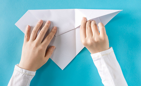 Person's hands folding a paper airplane on a blue background